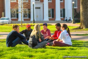 A diverse group of students is siting in a circle outside.
